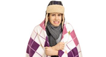 Young man covered with a blanket feeling cold isolated on white background