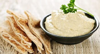"Try something new this year and make your own hummus. Made from five simple ingredients, its name in Arabic literally translates to ""chickpeas."" These cream-colored beans are full of protein and rich in fiber. Tahini is ground sesame seed paste that adds creaminess and a distinctive nutty flavor. Hummus can be served with pita bread or used as a dip for raw veggies like carrots, celery and bell pepper slices."