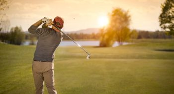 Man drives golf ball at dusk