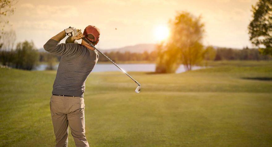 Man drives golf ball at dusk