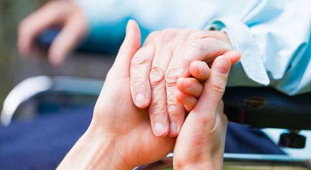 Caregiver holds a patient's hand.
