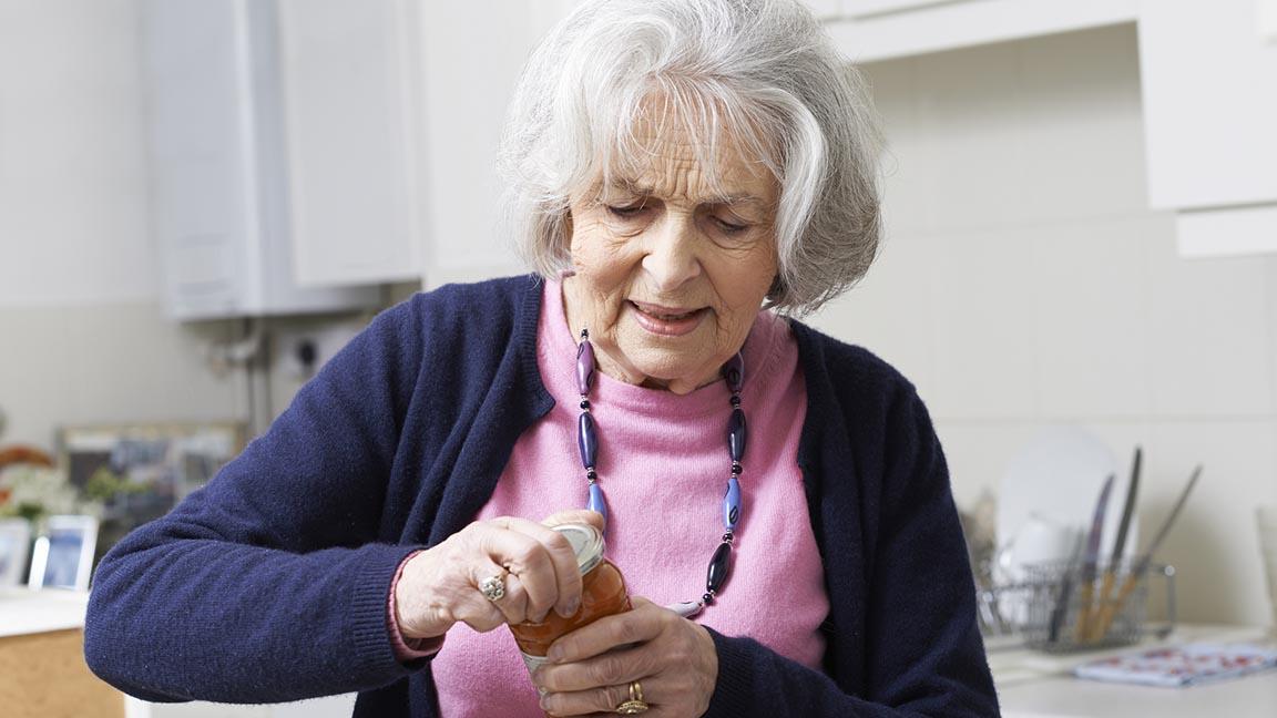 Woman struggles to open jar.