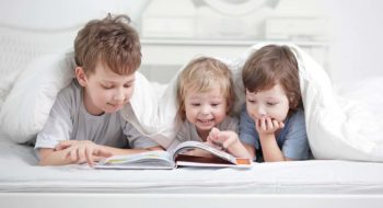 Three children read a book