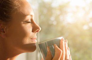 Woman enjoying coffee near a window.