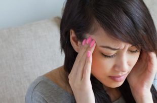 Woman suffers with migraine headache