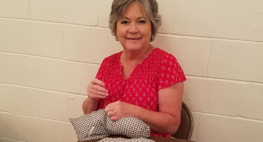 Breast cancer survivor Amanda Cribb helps craft one of the 212 post-surgical pillows donated by Pleasant Hill Baptist Church in Hemingway.