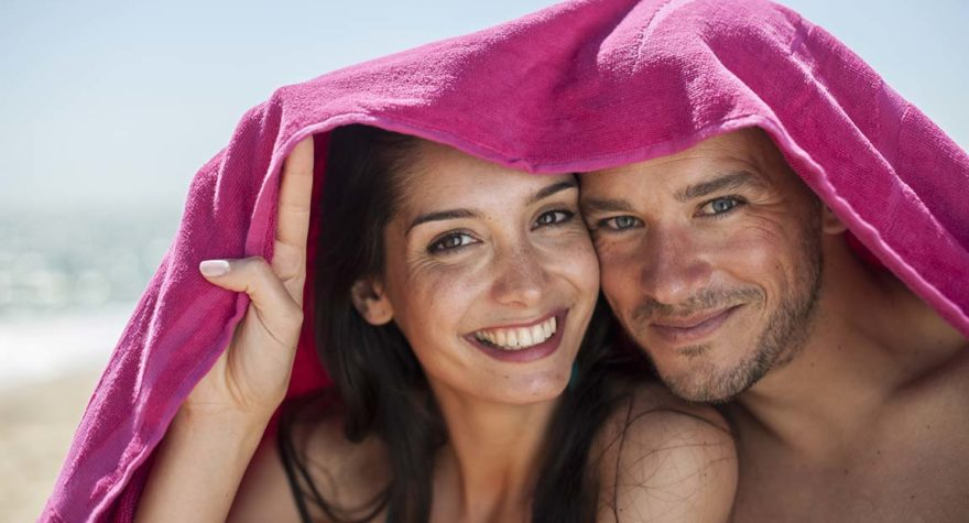 Couple on beach with towels on head.