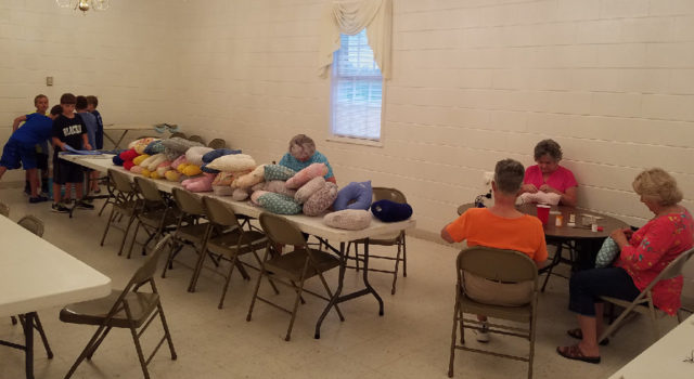 Members of the church and Vacation Bible School campers make pillows.