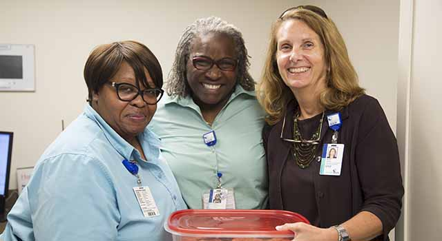 Beth Ward, executive vice president and chief financial officer for Tidelands Health, at right, delivers a container of freshly baked, homemade chocolate chip cookies to Tidelands Health team members fielding phone calls and helping keep patient records.