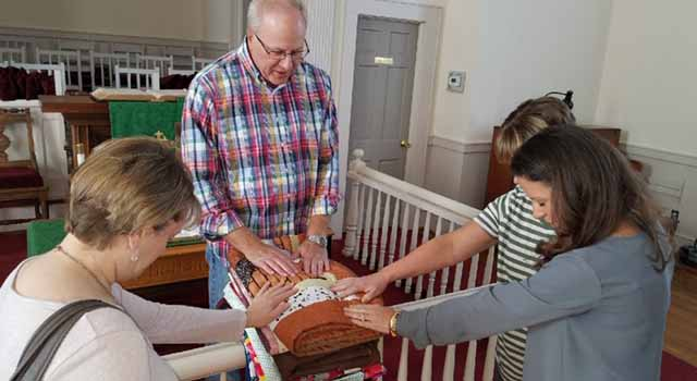 Socastee United Methodist Church Pastor Kurt McPherson blesses quilts created by the SUMC Stitchers. All quilts are blessed before they are donated.