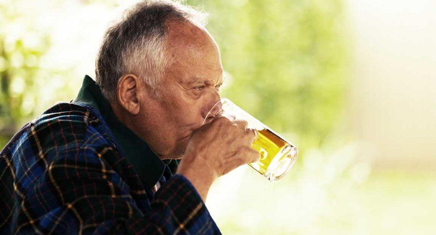 Senior consuming a beer.
