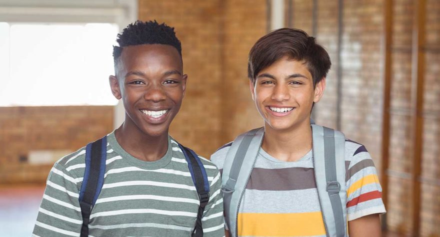 Two teens standing in a hallway