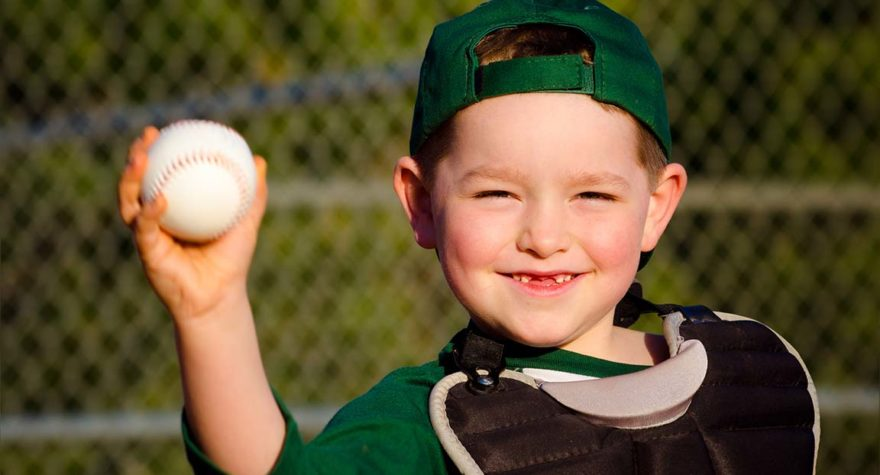 Young child in catcher's gear throwing baseball while laughing