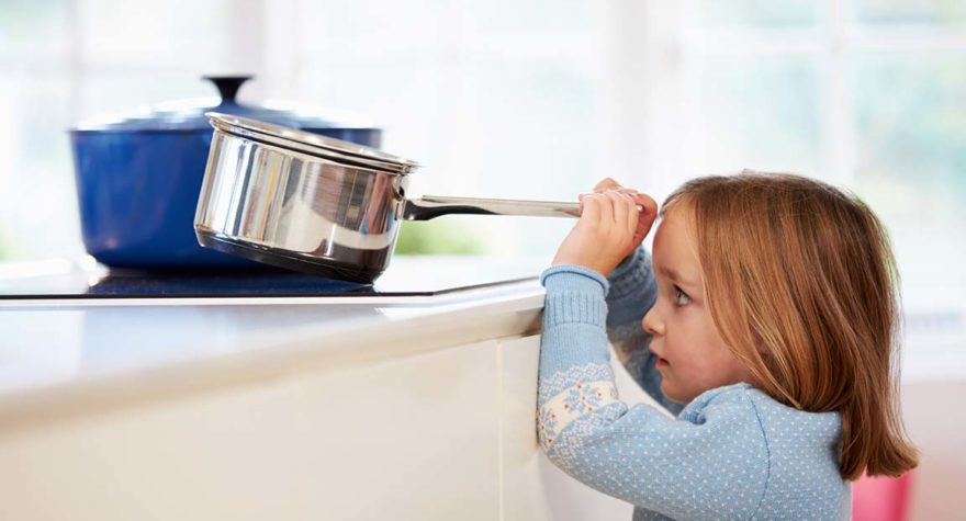Child risks injury removing pan from stove.
