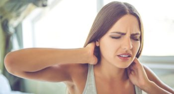 Woman struggles with neck pain.