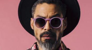 Portrait of a trendy man with silver beard, sunglasses and hat, isolated on pink studio background