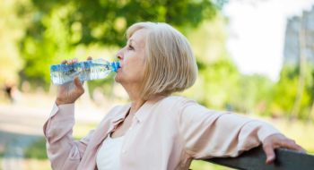 Adult woman is sitting in park and drinking water.