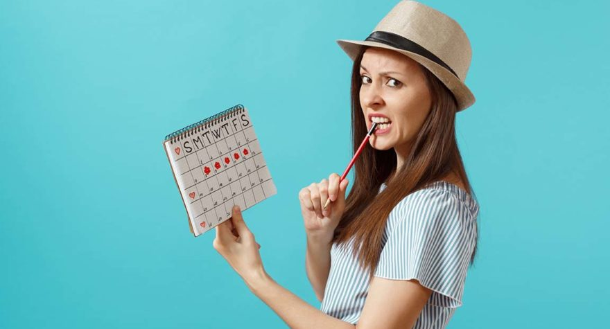 Portrait pensive woman in blue dress, hat holding red pencil, female periods calendar for checking menstruation days isolated on blue background. Medical healthcare, gynecological concept.