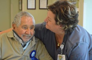 Deirdre Faulk, a nurse supervisor at Tidelands Health Rehabilitation Hospital, an affiliate of Encompass Health, embraces patient Oscar Sanchez during a party Saturday at the inpatient hospital celebrating his 100th birthday.