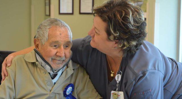 Deirdre Faulk, a nurse supervisor at Tidelands Health Rehabilitation Hospital, an affiliate of Encompass Health, embraces patient Oscar Sanchez during a party Saturday at the inpatient hospital celebrating his 100th birthday.