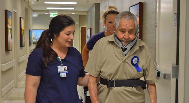 Patient Oscar Sanchez walks the hallway at Tidelands Health Rehabilitation Hospital, an affiliate of Encompass Health, on Saturday to his 100th birthday party with the help of occupational therapists Julianna Brown, left, and Karla Ehlers.