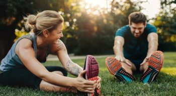 Man and woman stretching outdoors.