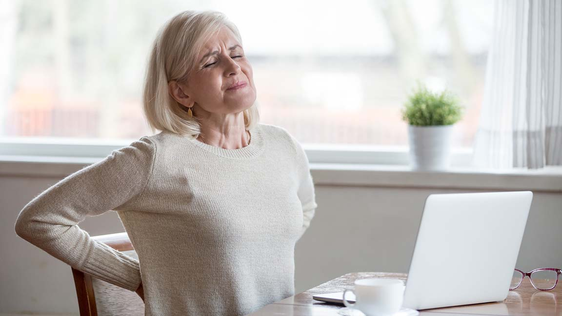 Woman struggles with back pain.