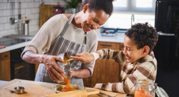 Son is helping mother to prepare pumpkin pie. American family. Single mother. Household chores for kids.