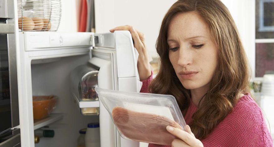 Concerned woman looks at meat.