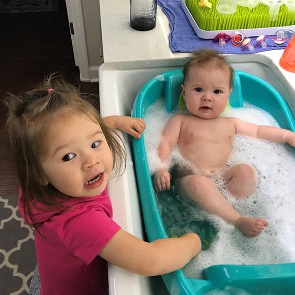 Older sister Nora, 2, likes to be around her baby sister, Luna, - bath or not.