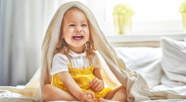 Child smiling on bed.