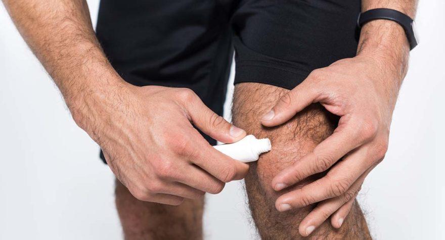 Man applying cream to knee.