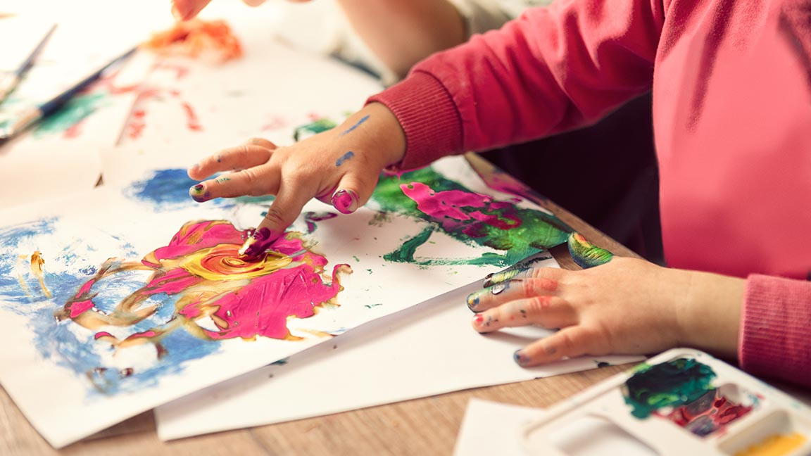Hands of painting little girl and the table for creativity