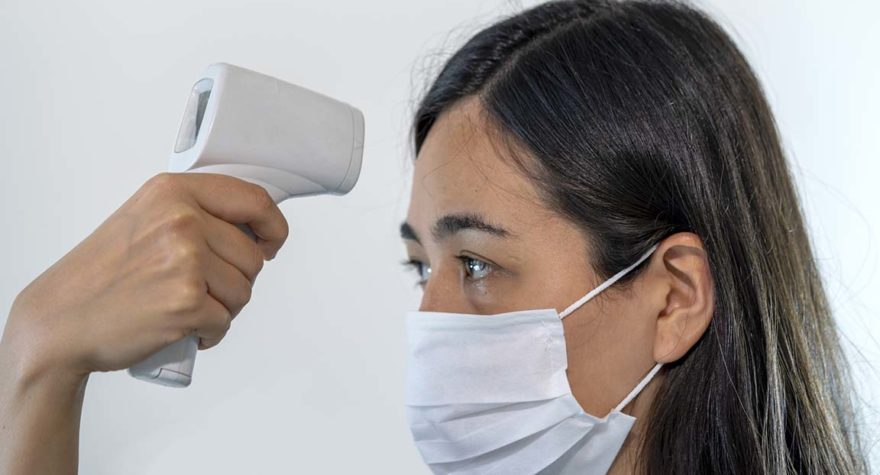 Taking a woman's temperature using an infrared thermometer