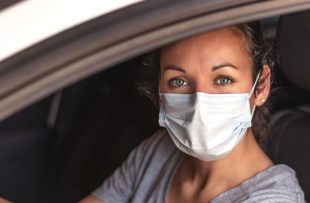 Young woman at drive-through with mask on.