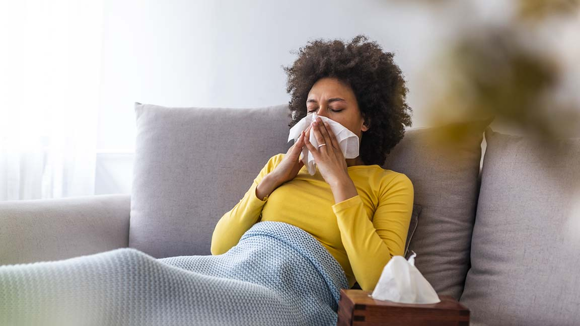 Woman on her couch blowing her nose