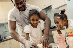 Father teaches daughters how to cook.