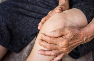 Older person holding knee
