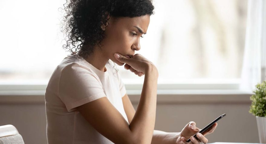 Worried woman conducts research on her phone.