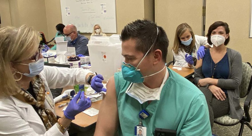 Dr. Christopher Bach, in scrubs, and his wife Amy Bach, an ER nurse practitioner, received the COVID-19 vaccine together.
