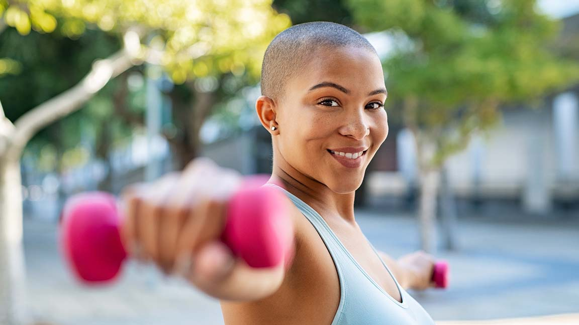 Woman exercising outside with weights