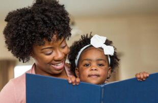 Woman reading book to child.