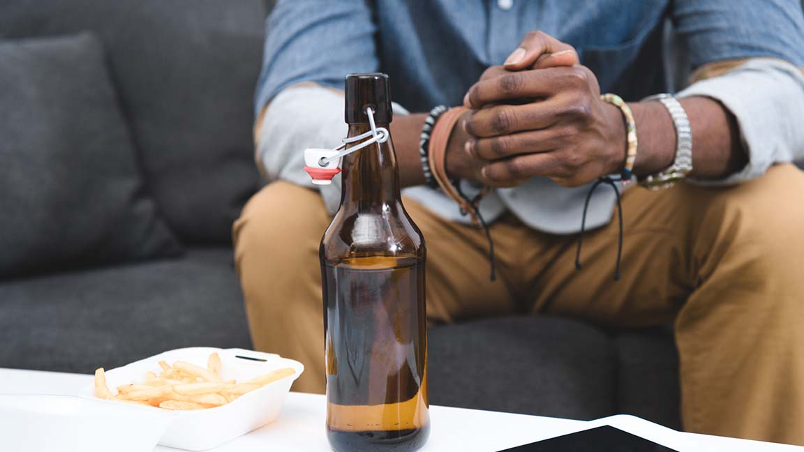 Man with beer on table.