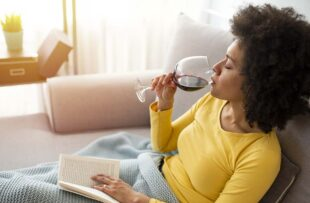 Woman reading a book and consuming wine.